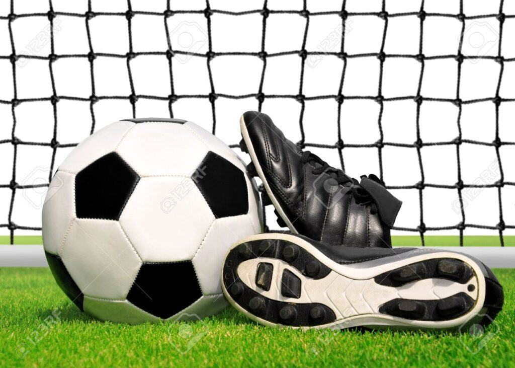 16225447 soccer ball and shoes in grass isolated